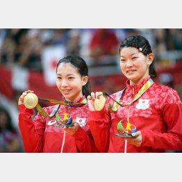 笑顔で金メダルを手にする高橋(右)と松友
